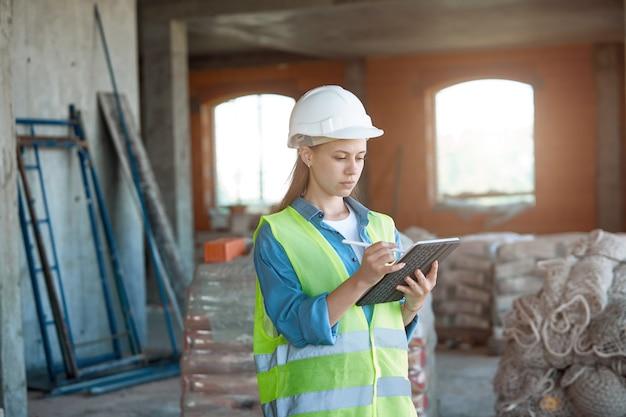 建設現場でタブレットを使って作業する女性エンジニアの仕事に夢中。若い建築家、保護具の肖像画。セレクティブフォーカス。