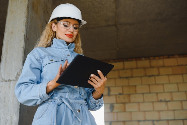 Absorbed in the work of a woman engineer working with a tablet on the background of the construction site. portrait of a young architect, protective equipment. selective focus.
