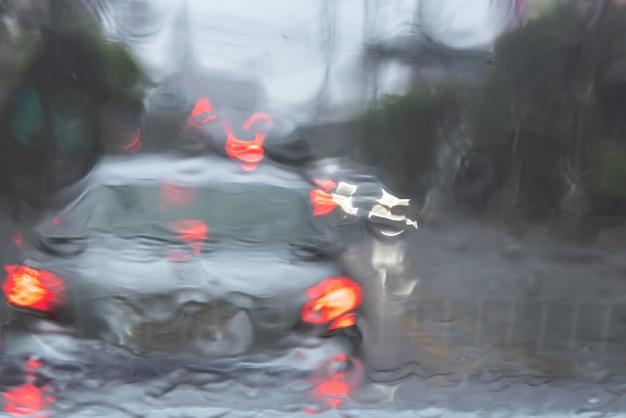 雨が降っているときに道路を運転している車の画像を抽象化してぼかします