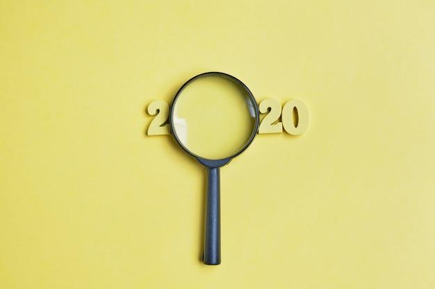 木製の数字と虫眼鏡の背景の抽象的な2020
