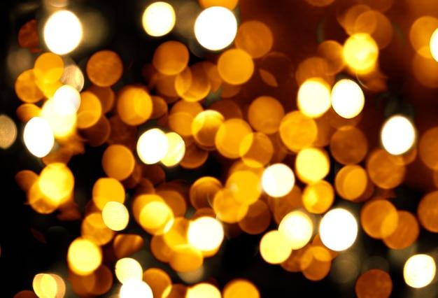 블랙에 흐릿한 황금 보케의 조명과 함께 추상 추상 축제 크리스마스 배경