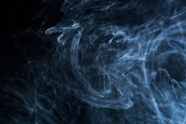 Abstract acrylic paint swirls in water on black space