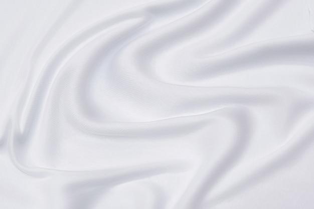 白またはアイボリー生地の背景、白の質感とディテールの抽象的でソフトフォーカスの波