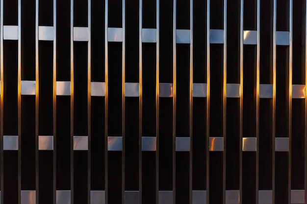 Abstract architectural detail of vertical lines with squares of metal at sunset.