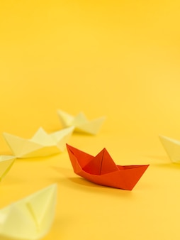 Abstract arrangement with paper boats on yellow background and copy space