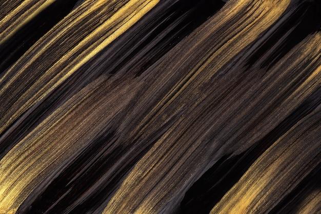 抽象芸術の背景の黒と濃い金色。黄色のストロークとスプラッシュとキャンバス上の水彩画。斑点模様の紙にアクリルアートワーク。テクスチャの背景。