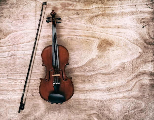 The abstract art background of classic violin and bow put on wooden board