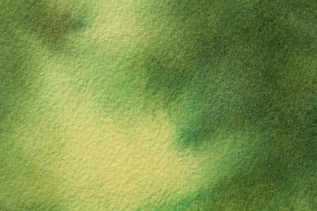 抽象芸術の背景の濃い緑と黄色の色。ソフトオリーブのグラデーションでキャンバスに水彩画。