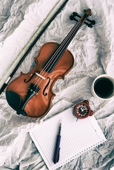 Abstract art design background of violin put beside red alarm clock and book, on grunge surface