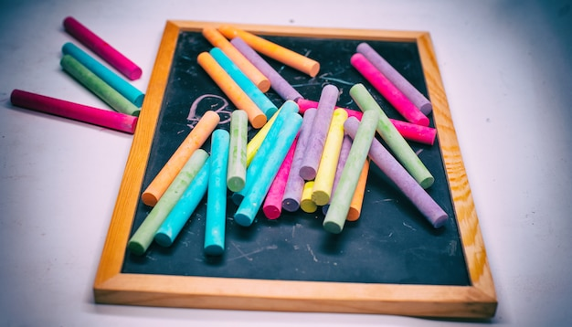 The abstract art design bakgroud of colorful chalks put on blackboard