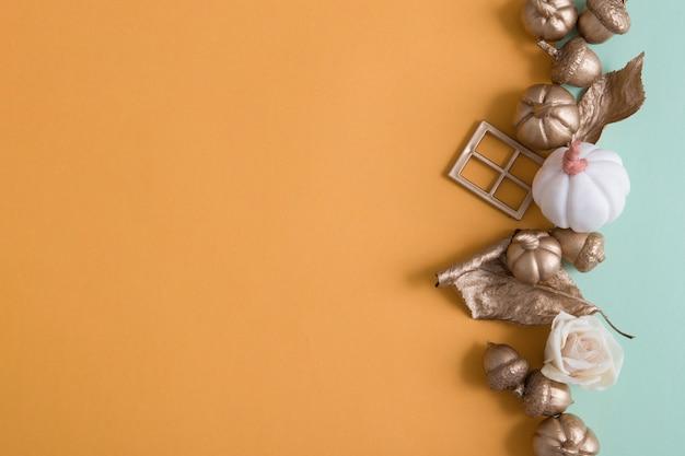 Абстрактный осенний фон с золотыми тыквами, листьями, желудями на цветных бумажных фонах с копией пространства
