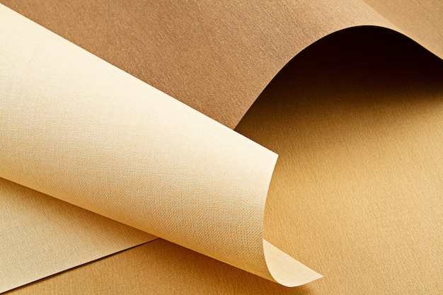 Abstract backgroud of rolled textured paper sheets of different shades of warm colors