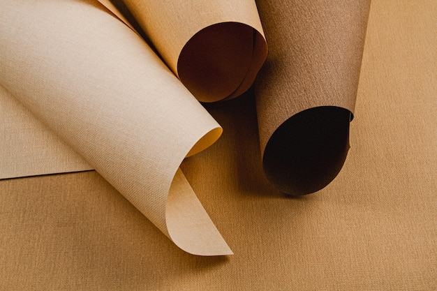 Abstract backgroud of rolled textured paper sheets of different shades