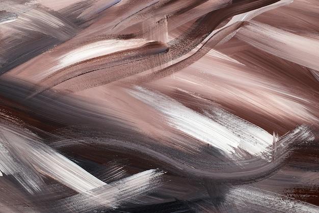 アクリル絵の具で無秩序に塗られた抽象的な背景。しっくいの質感のある濃い茶色、ベージュ、黒、黒のブラシのストロークの画像。