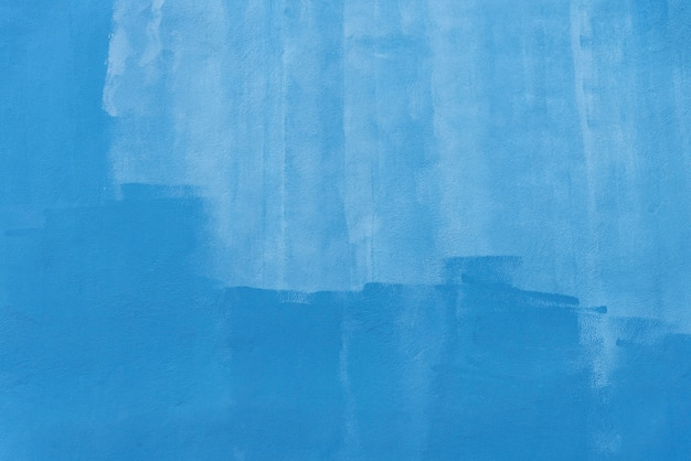 Abstract background from blue brush stroke painted on concrete wall.