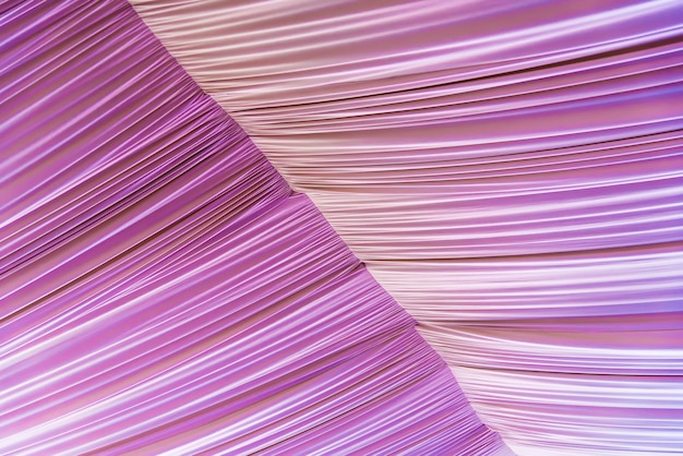 Abstract background from corrugated pink fabric on roof.