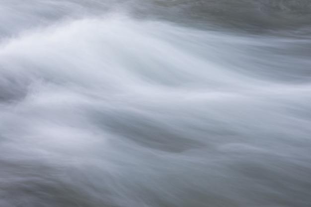 Абстрактный фон из длительного воздействия водного потока в горной реке крупным планом
