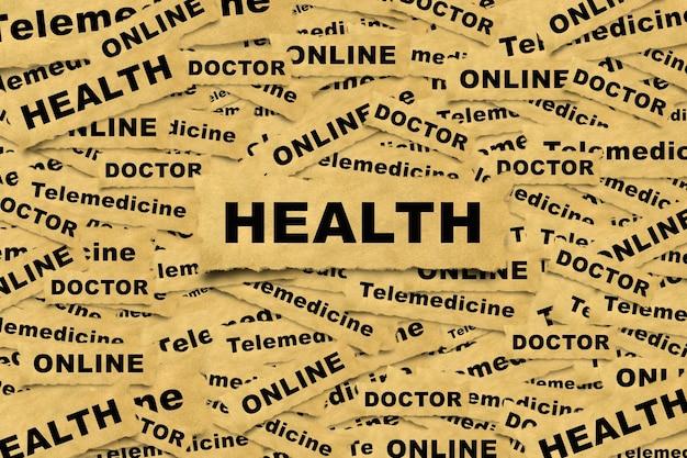 碑文の健康と関連する単語と紙片から抽象的な背景。