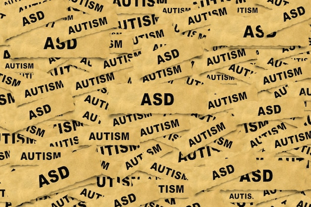 Abstract background from pieces of paper with the inscription asd autism spectrum disorder .