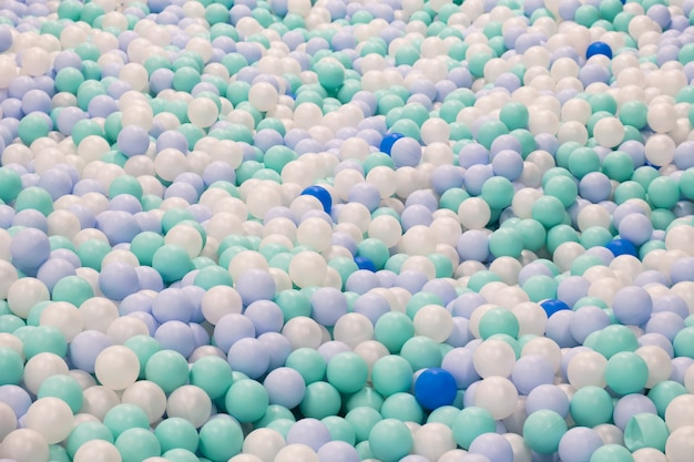 Abstract background from plastic balls of pastel white, blue and green colors