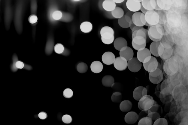 Abstract background of light white bokeh on a black night background.