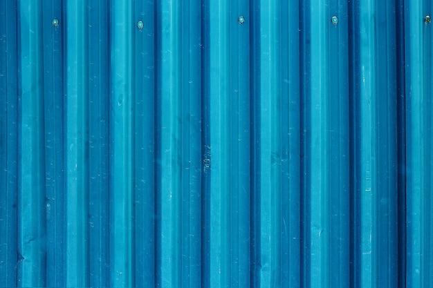 Абстрактный фон старой гофрированной металлической поверхности, окрашенной в бирюзовый цвет, крупным планом