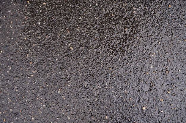 자갈이 포함 된 검은 젖은 아스팔트의 추상적 인 배경