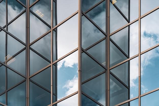 オフィスビルのガラス張りのコーナーに映る雲の抽象的な背景