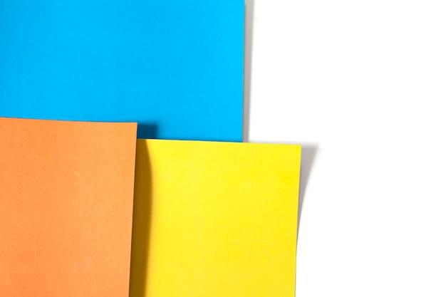 色紙の抽象的な背景:黄色、青、オレンジ。研究、工芸、趣味のコンセプト