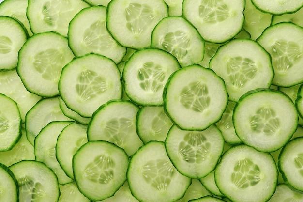白の緑のキュウリスライスの抽象的な背景