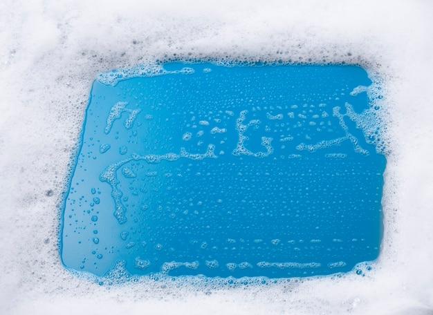 Абстрактный фон из мыльной белой пены и пузырей на синем фоне с местом для текста