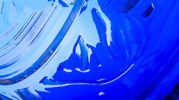 黒の背景にバケツとこぼれた青い絵の具の抽象的な背景。黒の背景に青い絵の具が注がれています。アーティストやクリエイティブなコンセプトに使用してください。こぼれた青い背景をペイントします。