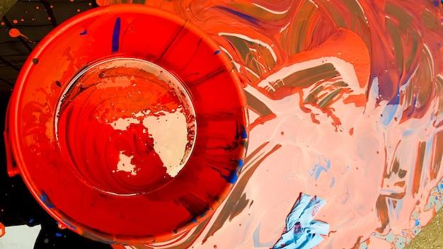 Абстрактный фон пролитой красной краской с ведрами на черном фоне. красная краска льется на черный фон. используйте его для художника или творческой концепции. краски пролили красный цвет фона.