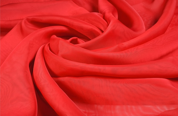 Абстрактный фон из закрученной, легкой, волнистой, красной, шифоновой ткани в форме розы