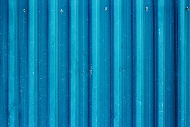 Abstract background of an old corrugated metal surface painted in turquoise close up