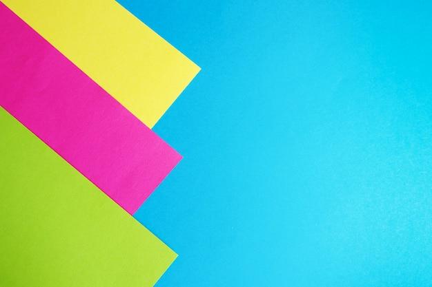 青の抽象的な背景のピンク、黄色、緑の紙。コピースペース。