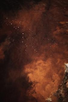 抽象的な背景、赤、オレンジ、茶色の星雲の色、創造的な液体の質感、暗闇と光、赤い川の水と水に浮かぶ塵