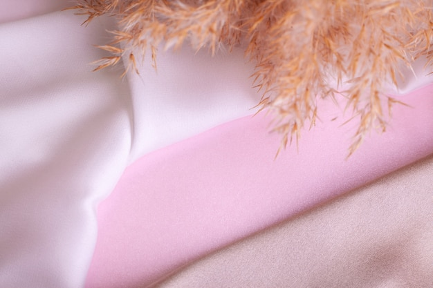 Abstract background in soft colors of silk fabrics on pink pearl paper and branch dry beige reed. beautiful trend texture.