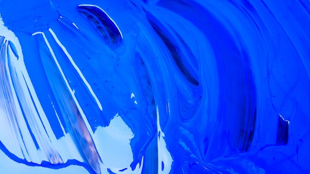 Abstract background of spilled blue paint with buckets on a black background. blue paint is pouring on a black background. use it for an artist or creative concept. paints spilled blue background.