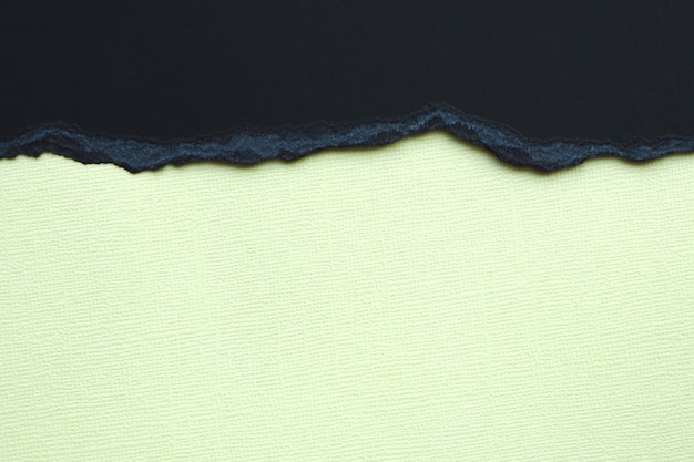 Abstract background and texture. black torn cardboard and light yellow texture paper.