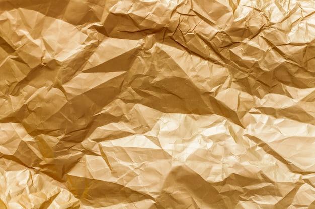 Абстрактная предпосылка текстуры золотого блестящего мятой фольги металлического листа.