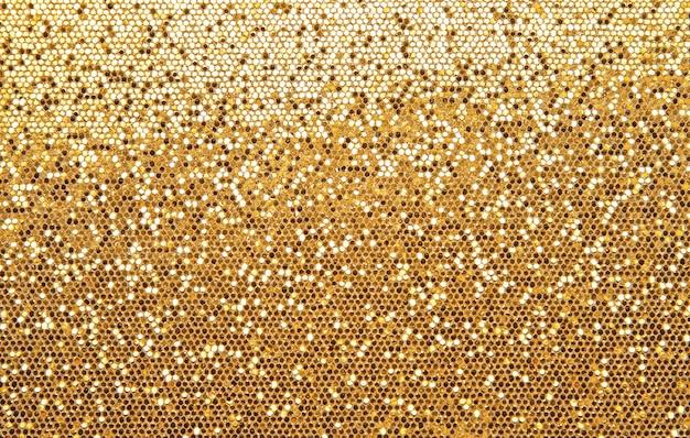 光沢のある金色のキラキラパターンの光のグラデーションの抽象的な背景テクスチャ
