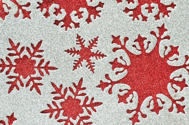 Abstract background and texture silver shiny material with cut out snowflakes of different shapes on a red shiny background.