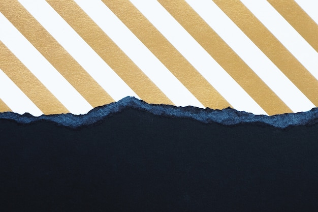 Abstract background and texture. torn black cardboard and striped gold and white paper.