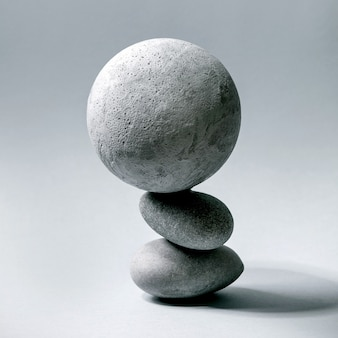 균형 잡힌 회색 기하학적 개체 구 및 돌의 구성으로 추상적인 배경. 공간을 복사합니다. 제품 프레젠테이션을 위한 현대적인 개념입니다. 광장