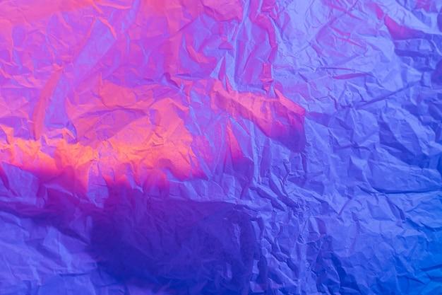 ネオングラデーションでしわくちゃの紙と抽象的な背景。鮮やかなブルー、ピンク、オレンジの色