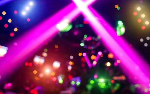 현대 디스코 파티 나이트 클럽에서 레이저 쇼의 디포커스 보케가 있는 추상적 배경
