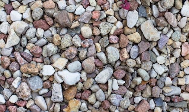 さまざまな形の色とりどりの小さな小石の石で抽象的な背景