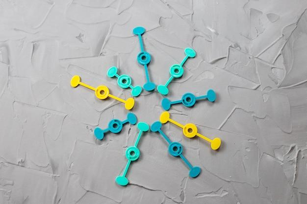 Абстрактный фон с пластиковыми цветными частями на сером бетоне может символизировать части целого