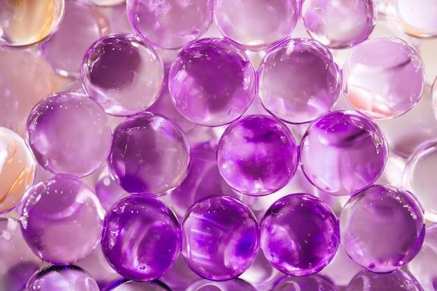 紫と青の色の光沢のある水球と抽象的な背景